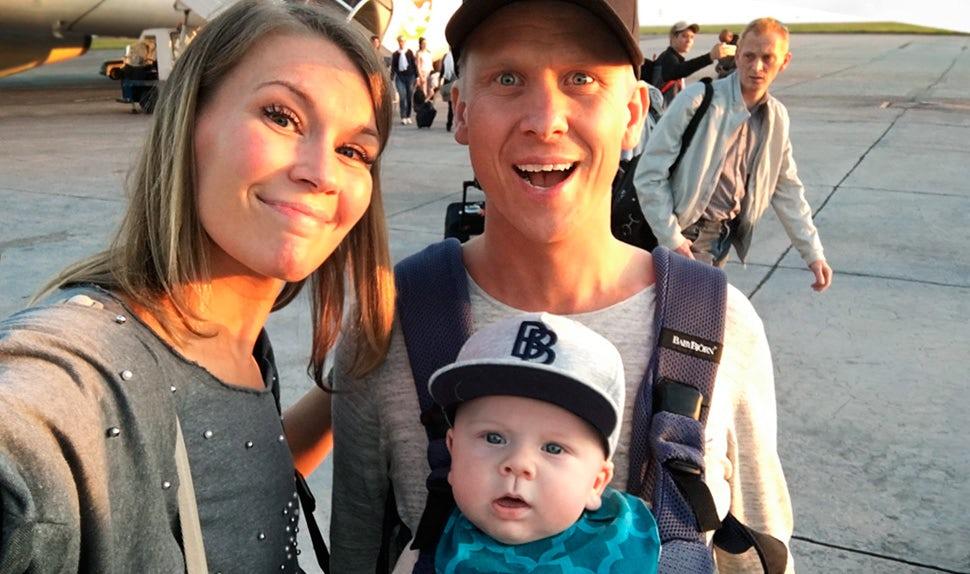 Magazine BABYBJÖRN – Petra Månström en voyage avec son bébé que son partenaire porte ici dans un porte-bébé.