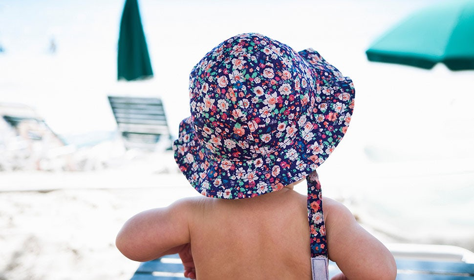 BABYBJÖRN Magazine – Travel with an infant is exciting – child on the beach in a sun hat.