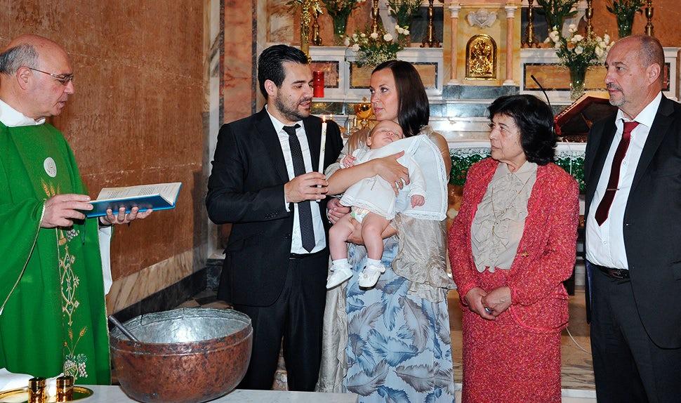Magazine des parents BABYBJÖRN – Le prêtre versant de l'eau sur la tête de leur fille lors du baptême religieux.