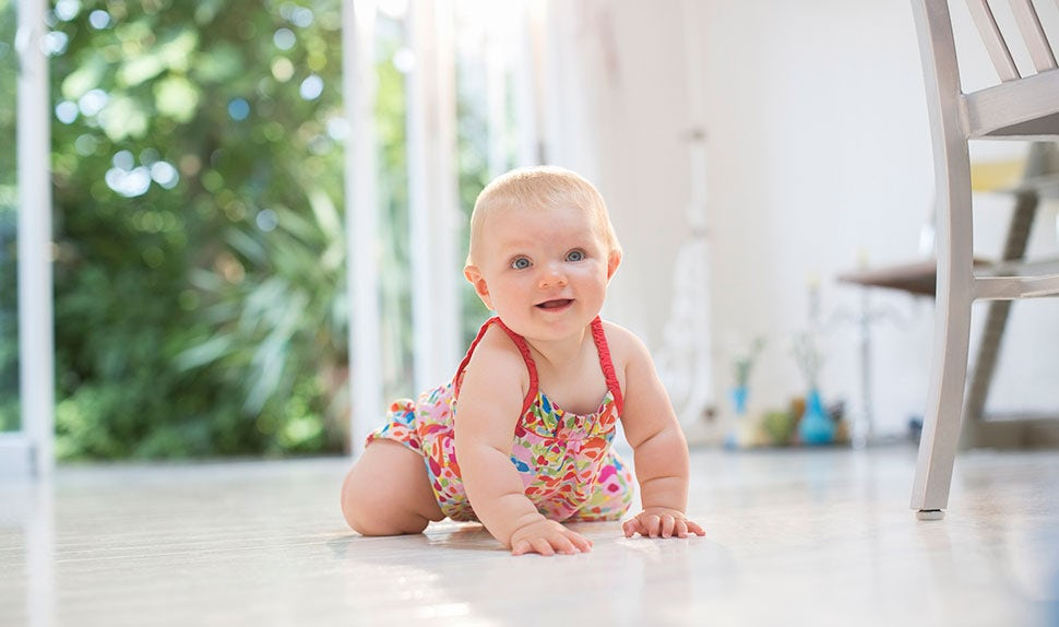 BABYBJÖRN Magazine – When do babies crawl? A little baby learning how to crawl, roll or scoot around.