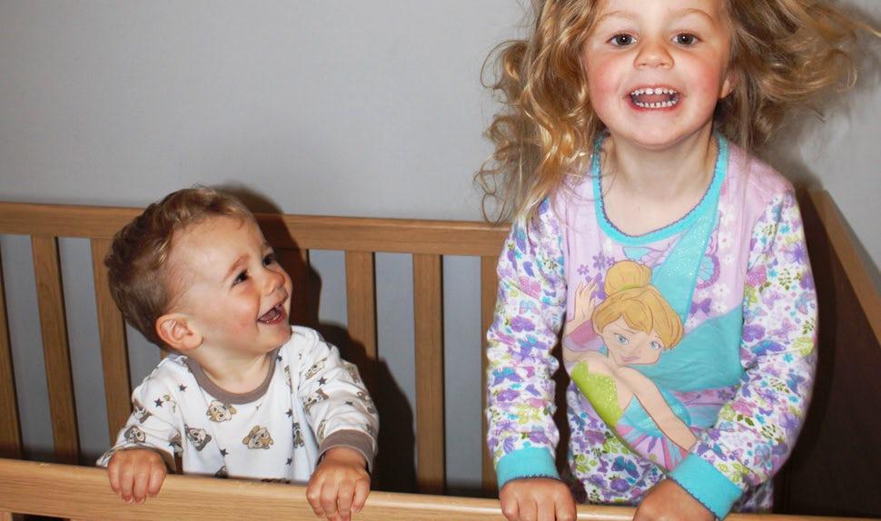BABYBJÖRN Magazine – Baby not sleeping – two happy, wide-awake siblings in a crib.