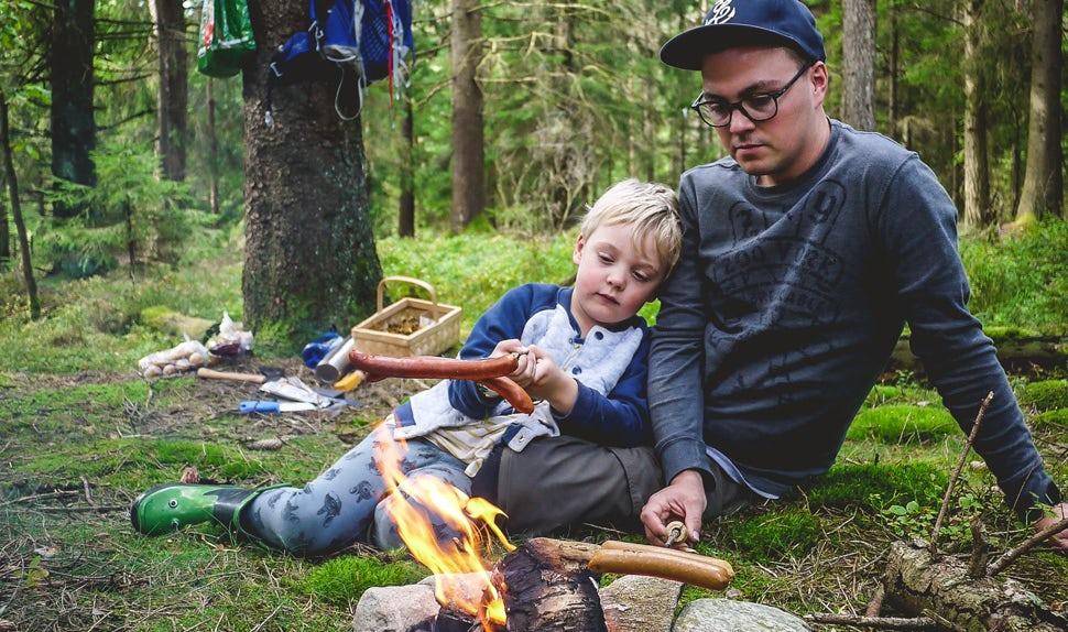Magazine BABYBJÖRN– Joacim et Karolina qui forment la famille Matkoma prennent autant de plaisir à préparer les repas en plein air qu'à la maison près de la cheminée.