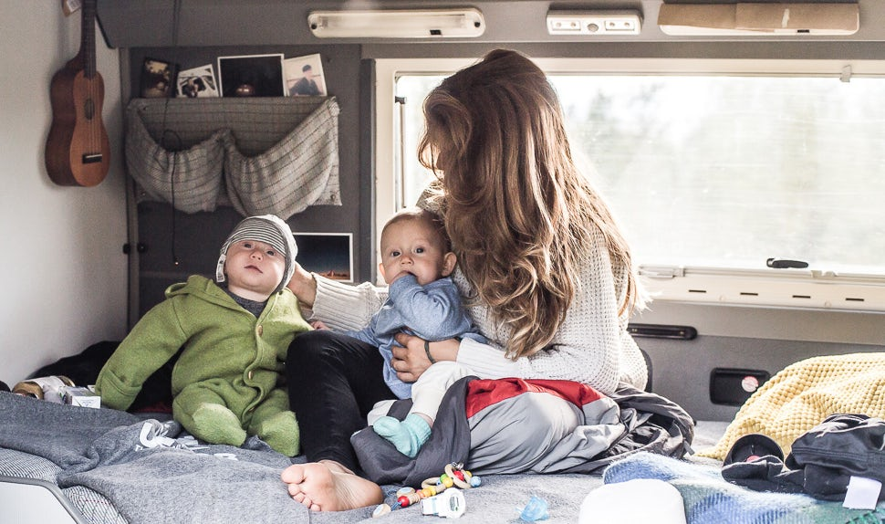 BABYBJÖRN Magazine – Mom Juli and her twin daughters sitting inside the camper van.