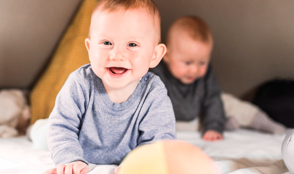 BABYBJÖRN Magazine for Parents – Happy twins play in the camper van's loft bed.