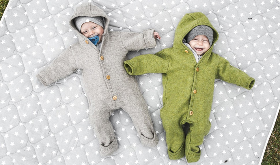 BABYBJÖRN Magazine – Twin babies Lovisa and Matilda play on a blanket outdoors.
