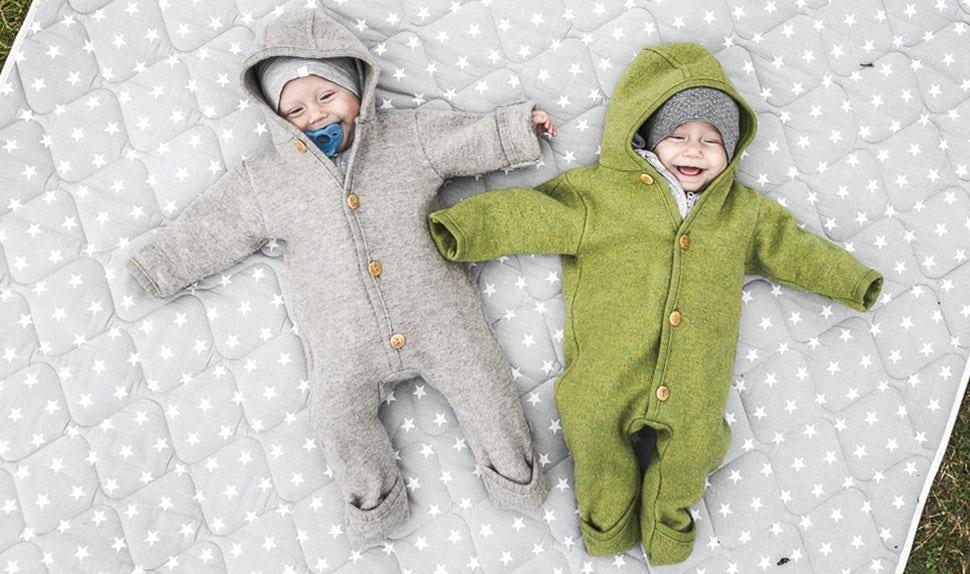 Magazine BABYBJÖRN – Les jumelles, Lovisa et Matilda, jouent sur une couverture à l'extérieur.