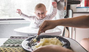 BABYBJÖRN Magazine – One of the babies sits in a high chair and watches expectantly as food is prepared.