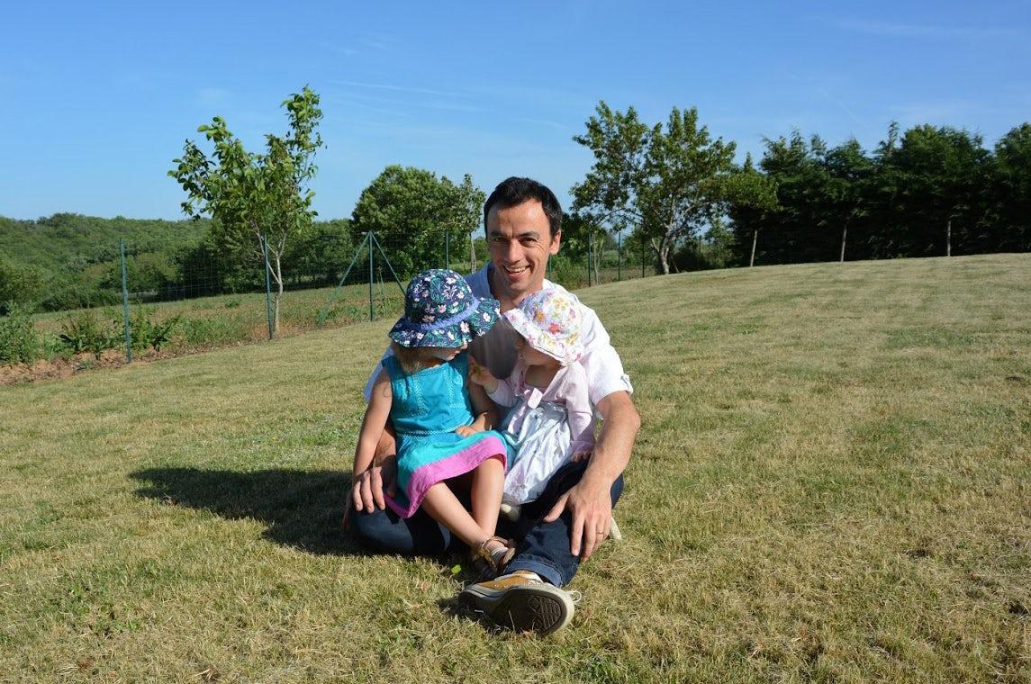 Magazine BABYBJÖRN – Le soleil brille et Pierre est assis dans l'herbe avec ses deux filles sur les genoux.