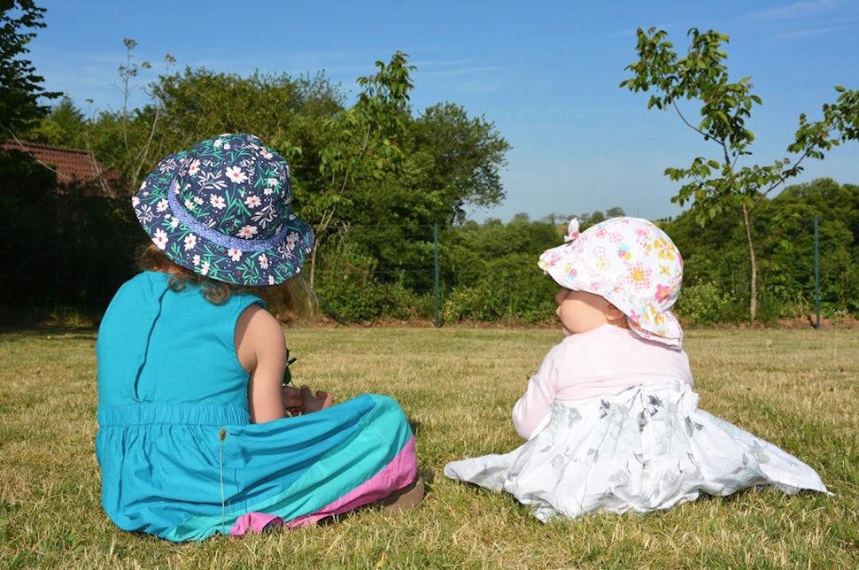 Magazine BABYBJÖRN – Les sœurs Luna et Maëlie assises dans l'herbe, tournant le dos à la caméra.