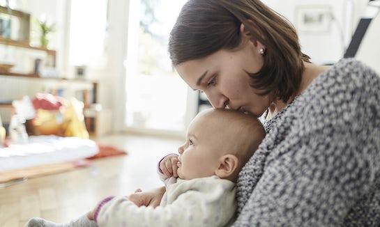 BABYBJÖRN Magazine – Une mère atteinte de dépression post-partum assise sur le sol avec son bébé.