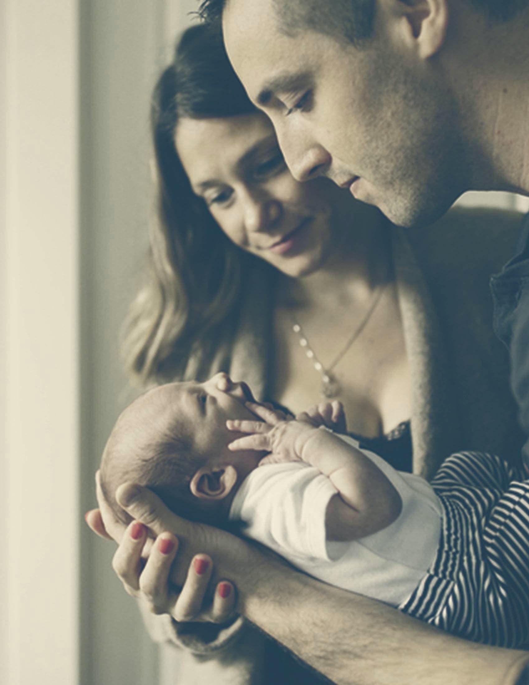 Deux parents tiennent et regardent leur bébé | BABYBJÖRN