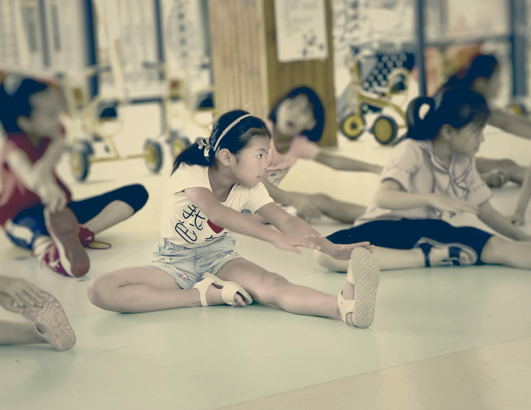 Photo de Mor Lee et d'autres enfants qui font des exercices d'étirement au sol. | BABYBJÖRN