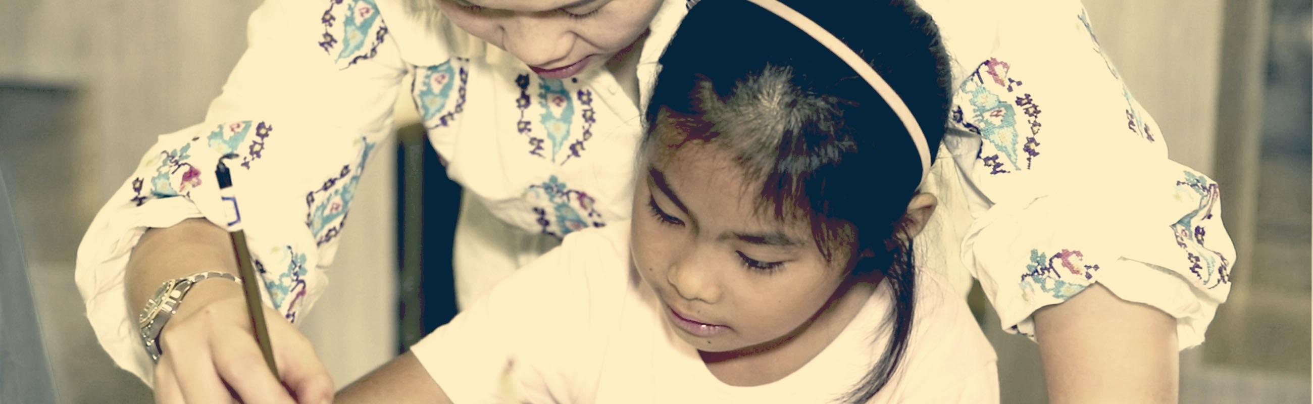Une enseignante montre à un enfant comment tenir son pinceau | BABYBJÖRN