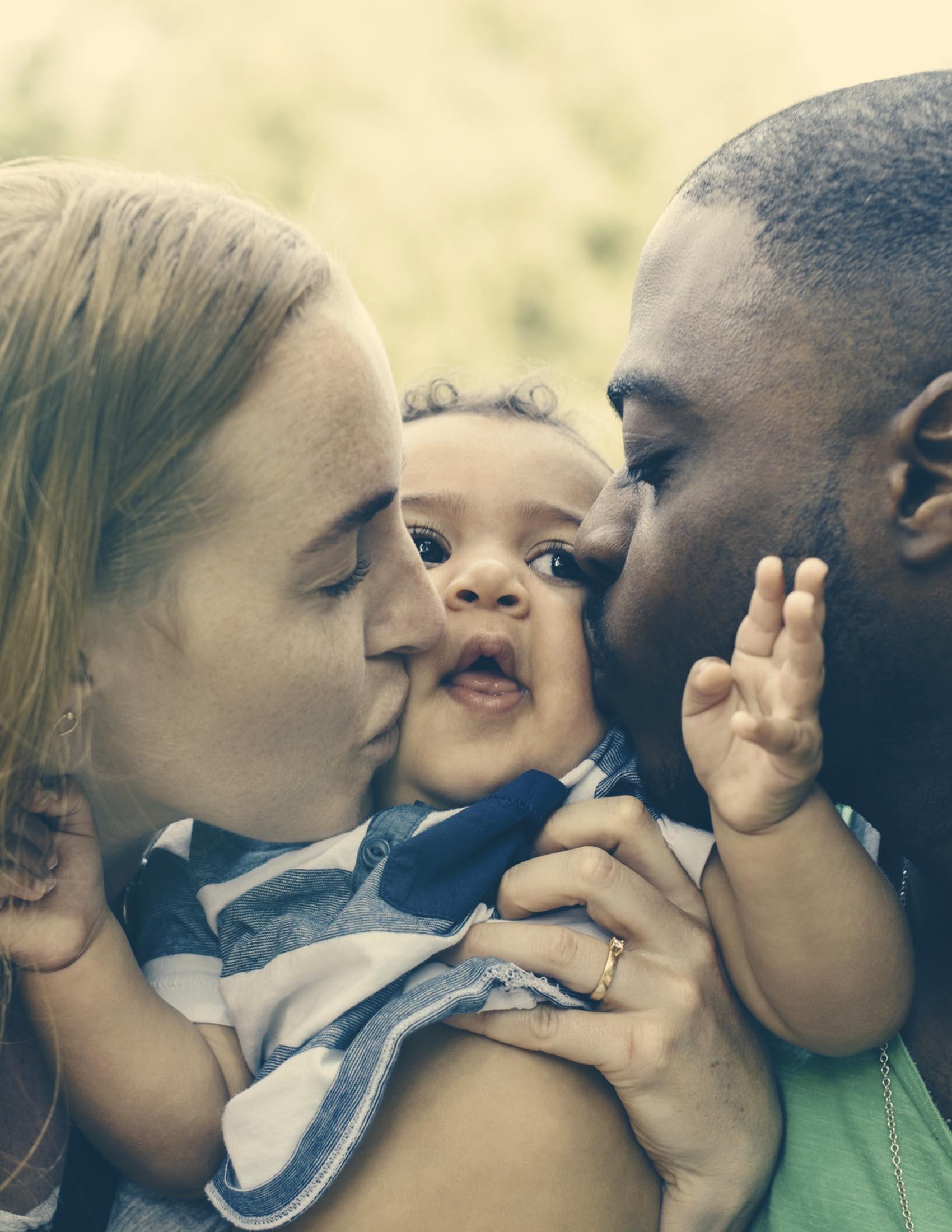 Bébé est embrassé sur les deux joues par ses parents | BABYBJÖRN
