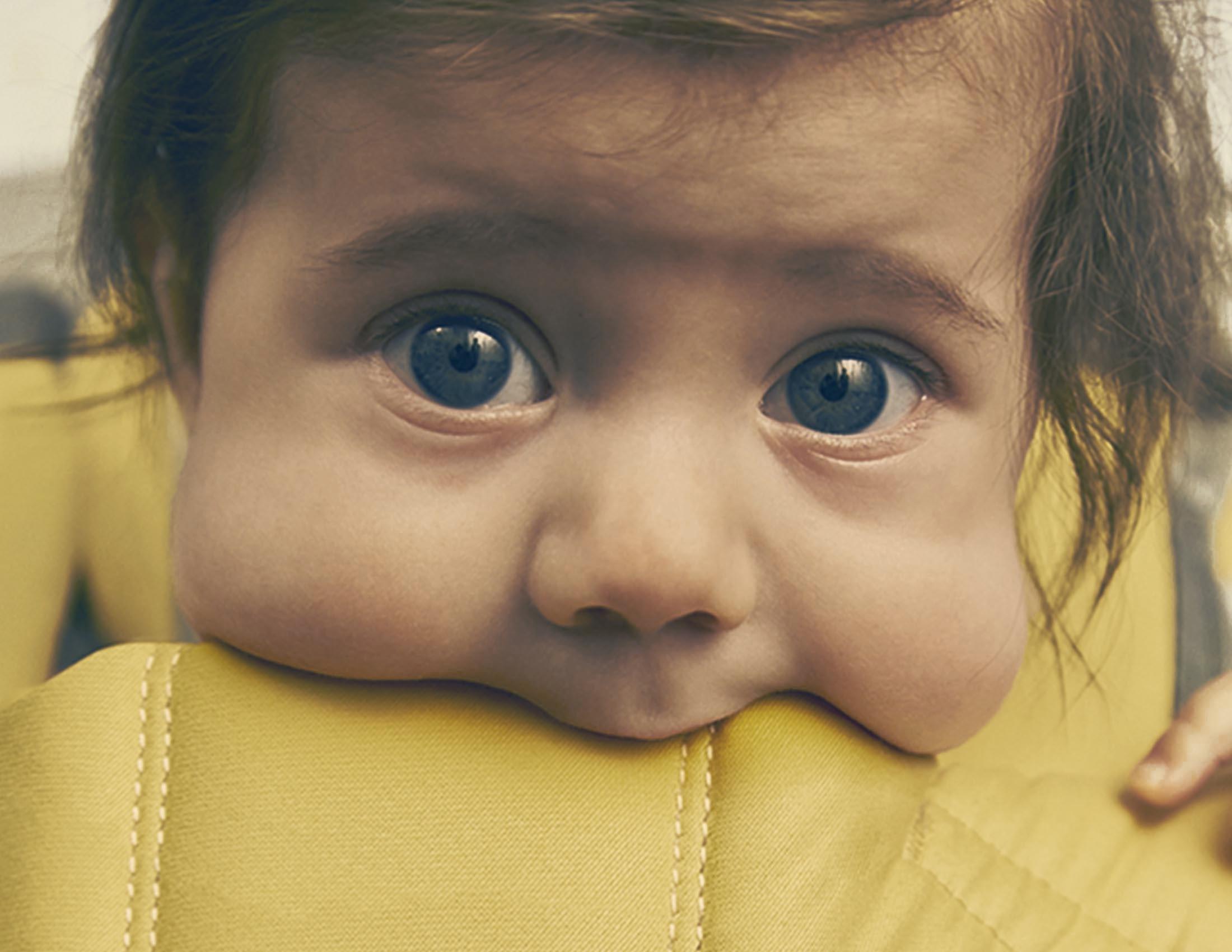 Bébé suce le bord d'un porte-bébé One de BABYBJÖRN
