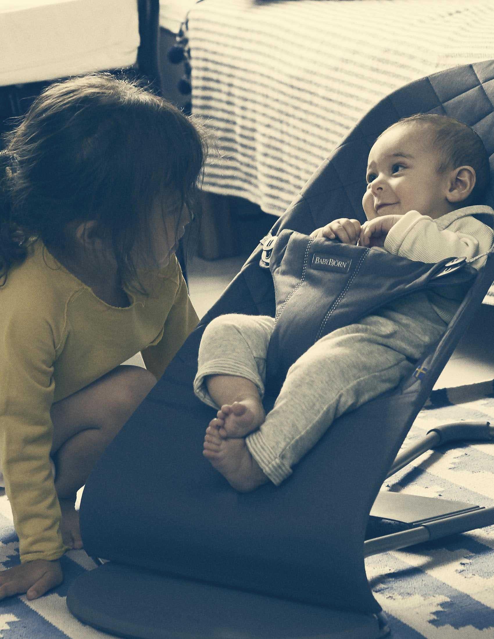 Un bébé se repose dans un siège sauteur Bliss de BABYBJÖRN et est diverti par sa grande sœur | BABYBJÖRN