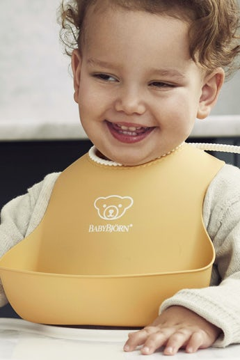 Baby Bib, Powder yellow, with deep spill pocket to catch any mess - BABYBJÖRN